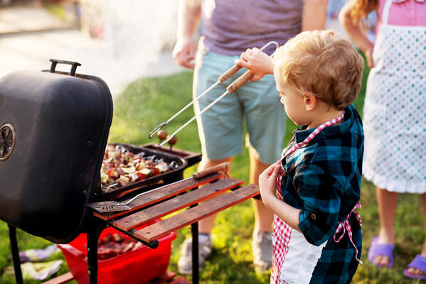 Kid grilling at outside cookout