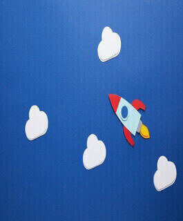 Paper rocket on blue background