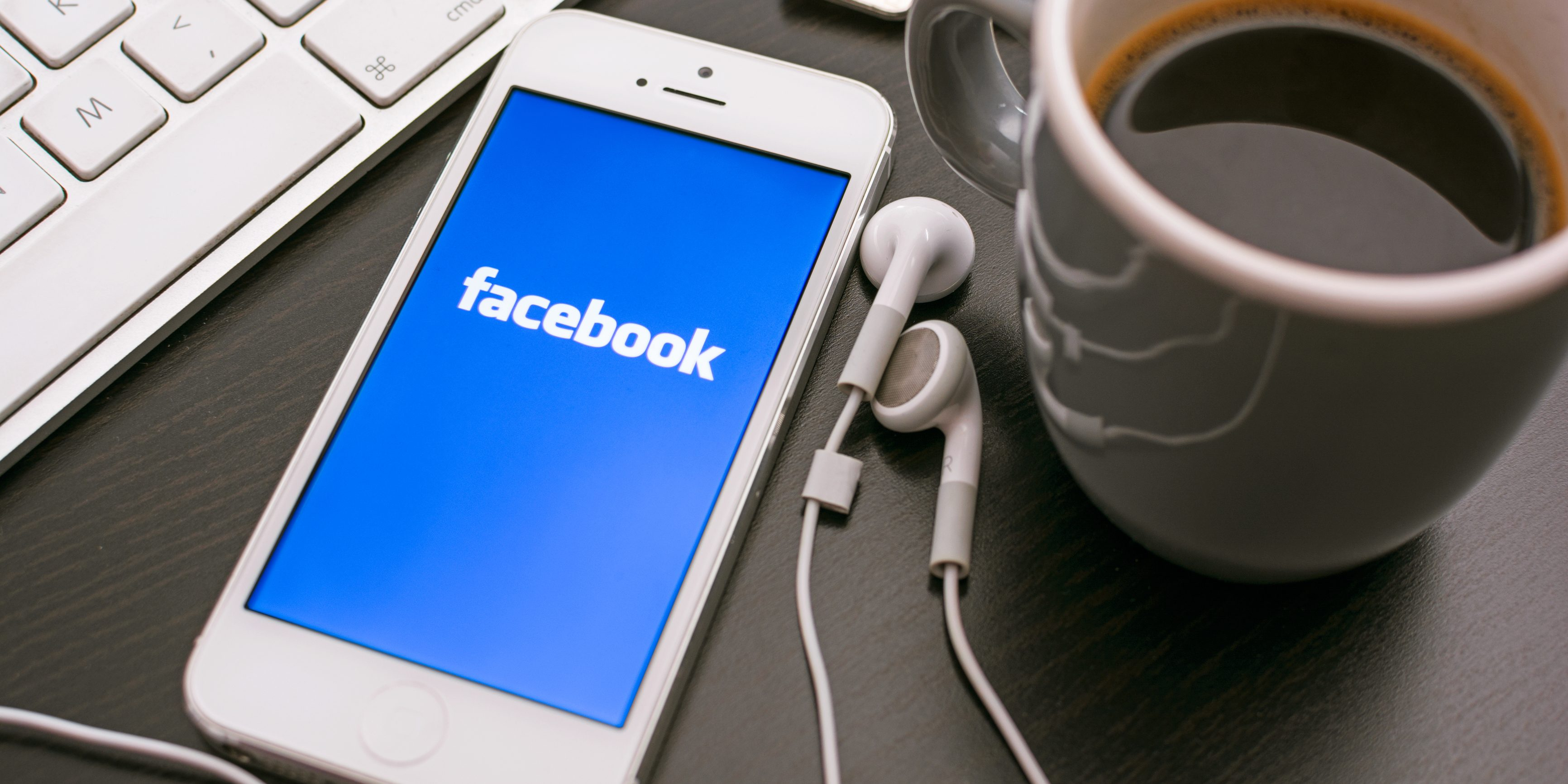Phone displaying Facebook app with earbuds and coffee mug