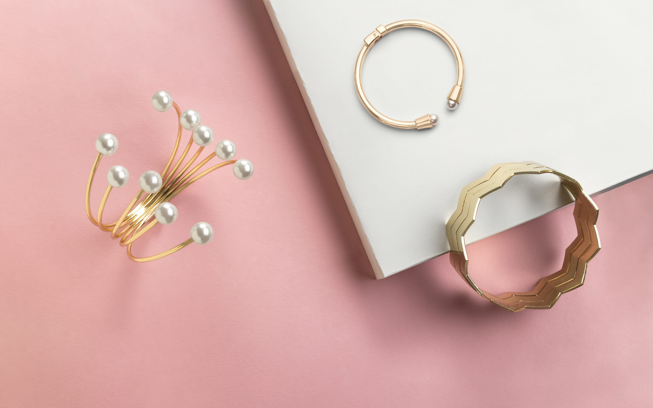 Gold jewelry against pink and white background