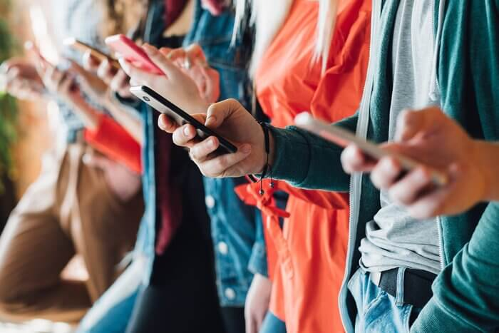Closeup of group of people holding smartphones