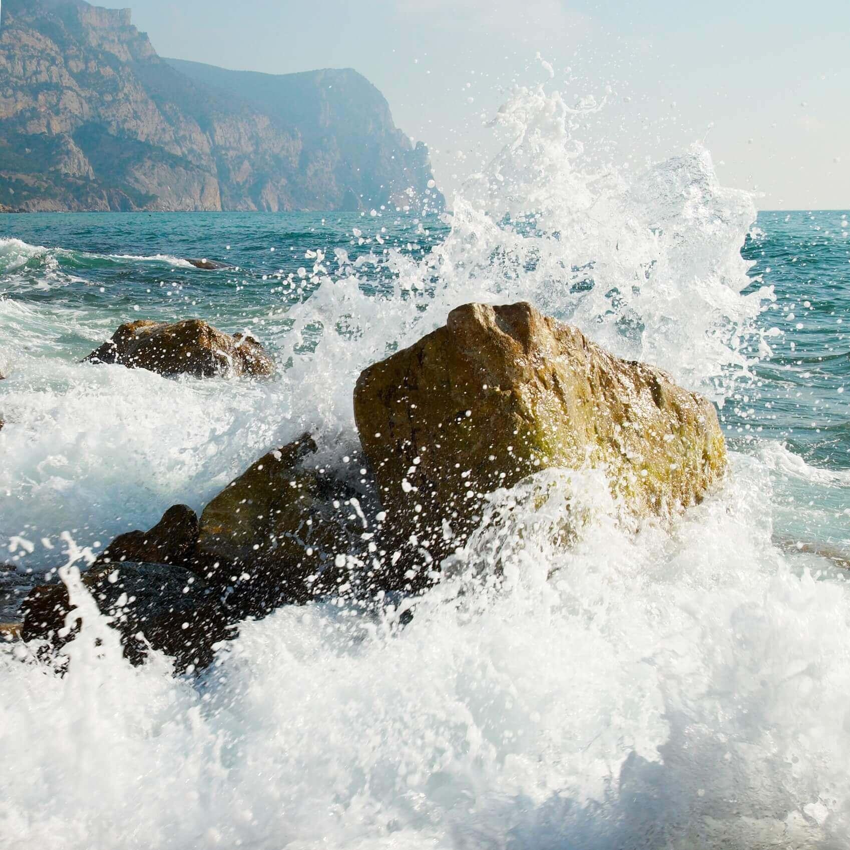Ocean wave crashing against a rock